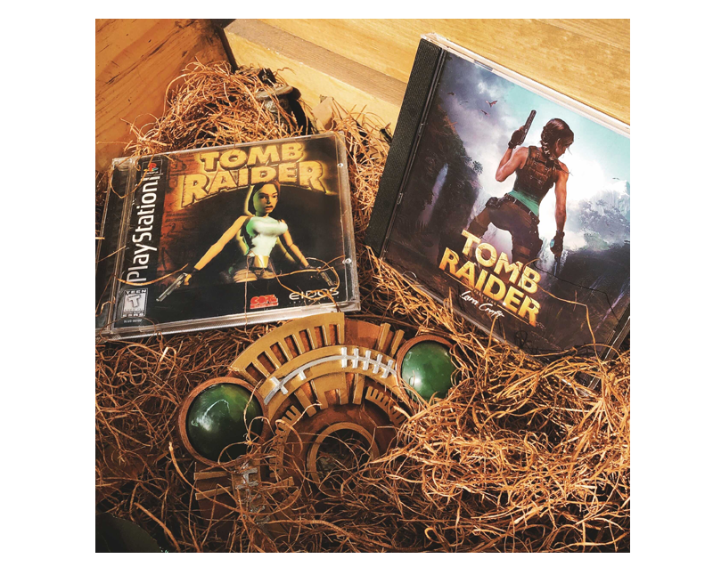 A picture of two PlayStation cases with bold old and new 1996 Tomb Raider box arts and a Scion prop in a basket with straw.