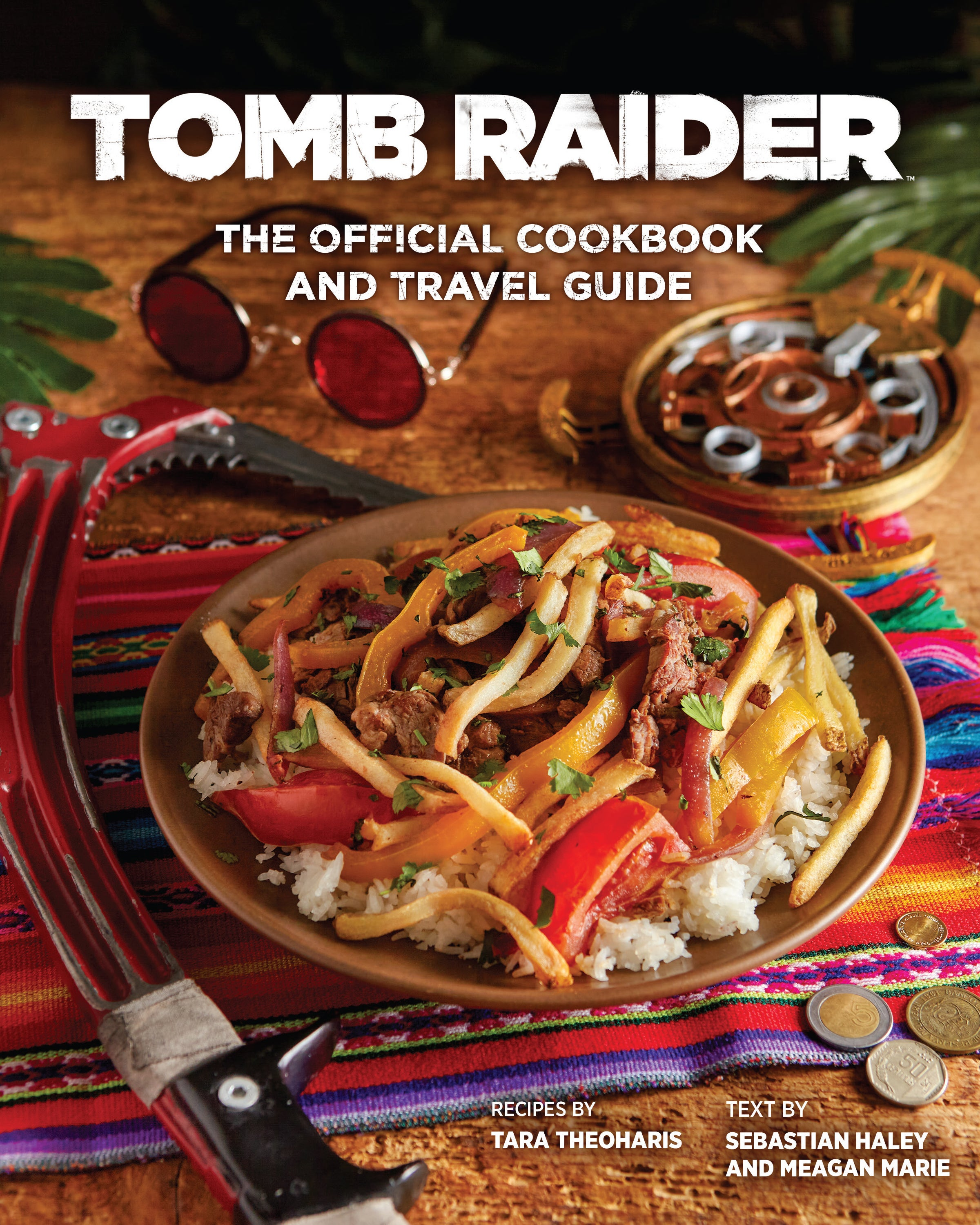 A graphic of the front cover of the upcoming Tomb Raider cookbook and travel guide. It shows a bowl of food surrounded by varied Tomb Raider artifacts, like Lara's classic round glasses or her survivor trilogy climbing axe.
