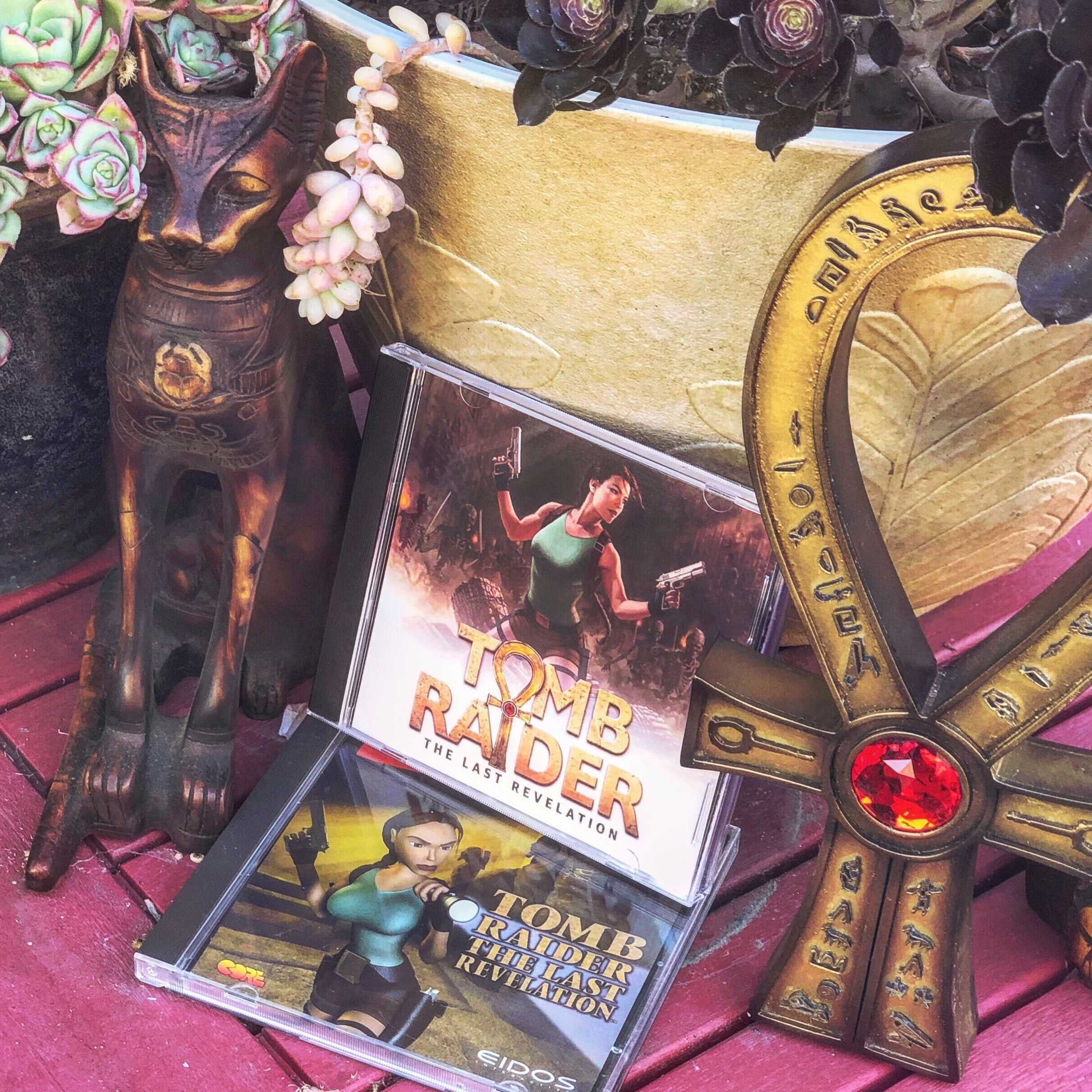 A photo of the new reimagined TRIV box art and original box art in jewel cases. They are next to Sphinx and the Amulet of Horus props.