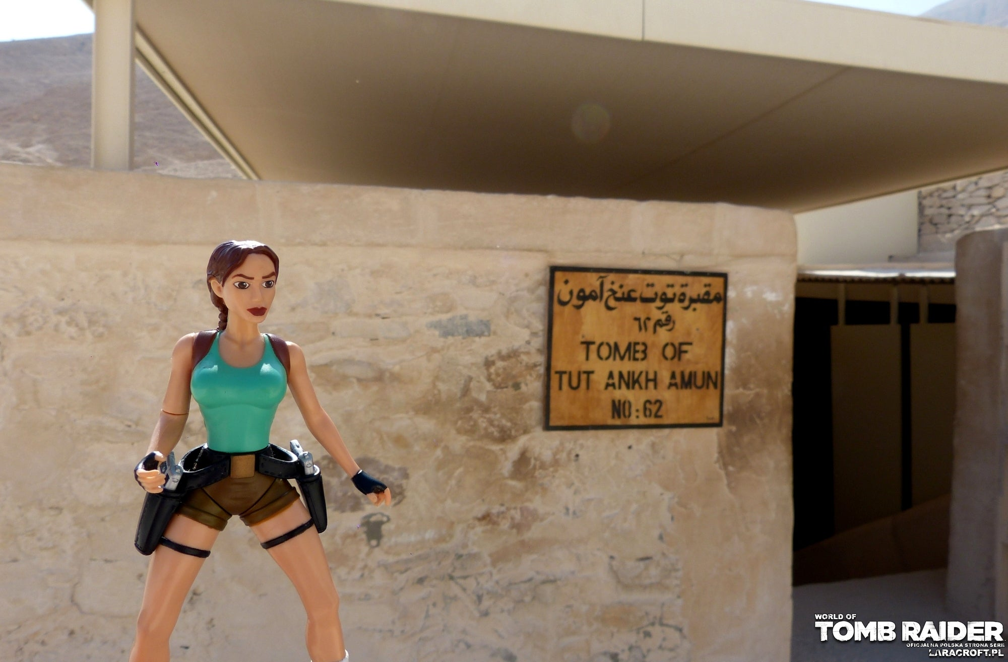 A photograph of a Lara Croft figure in front of a tomb sign in Egypt