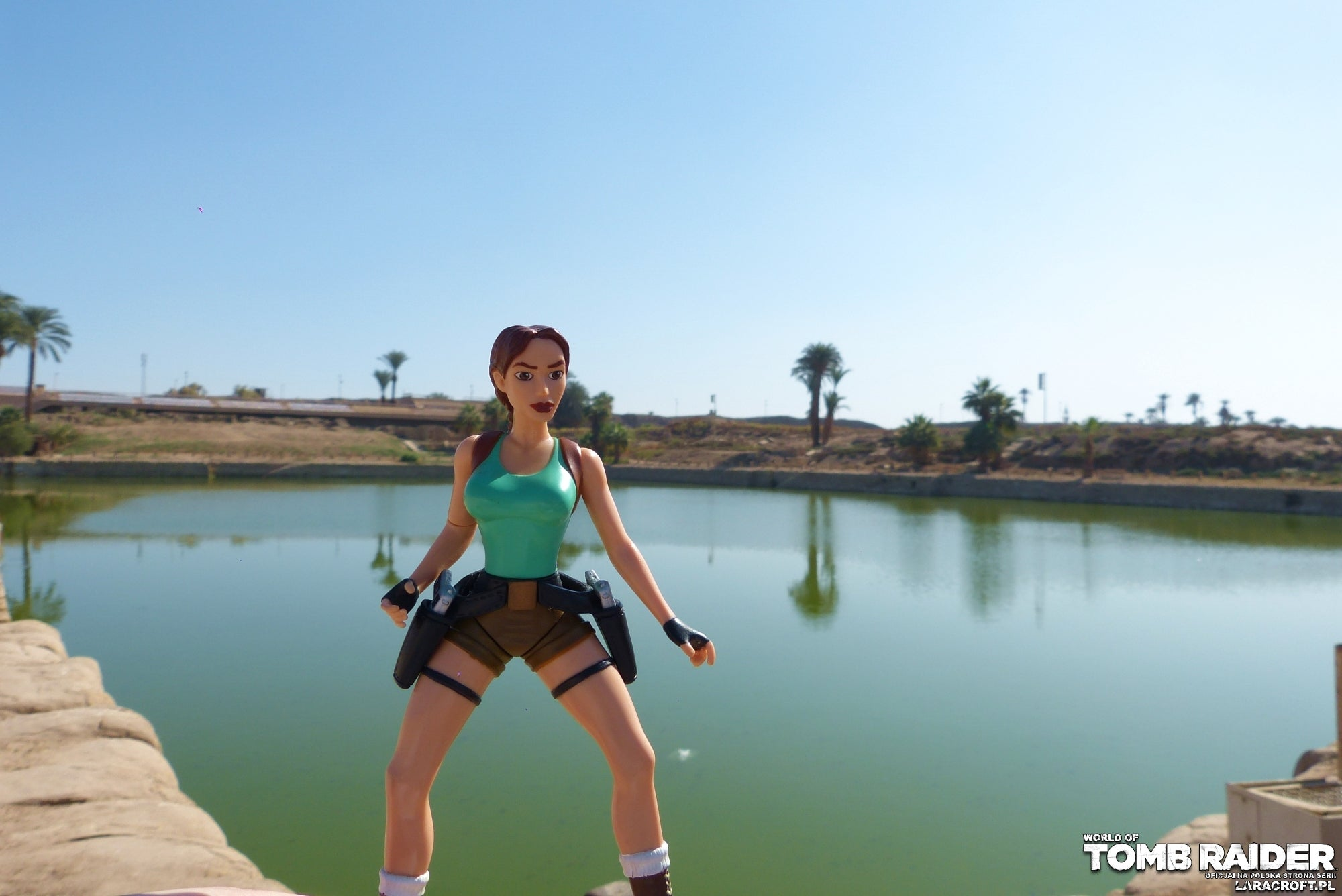 A photograph of a Lara Croft figure in front of the Sacred Lake in Egypt