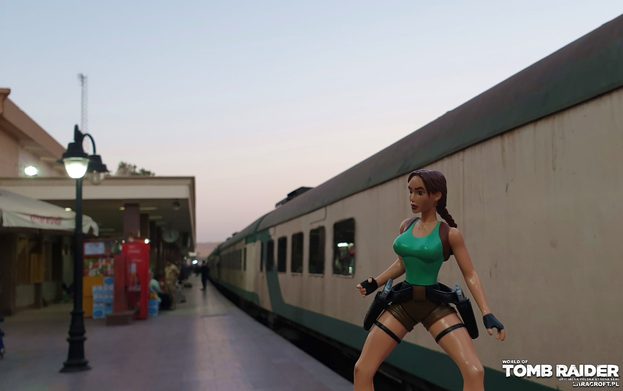 A photograph of a Lara Croft figure in front of a desert railroad in Egypt