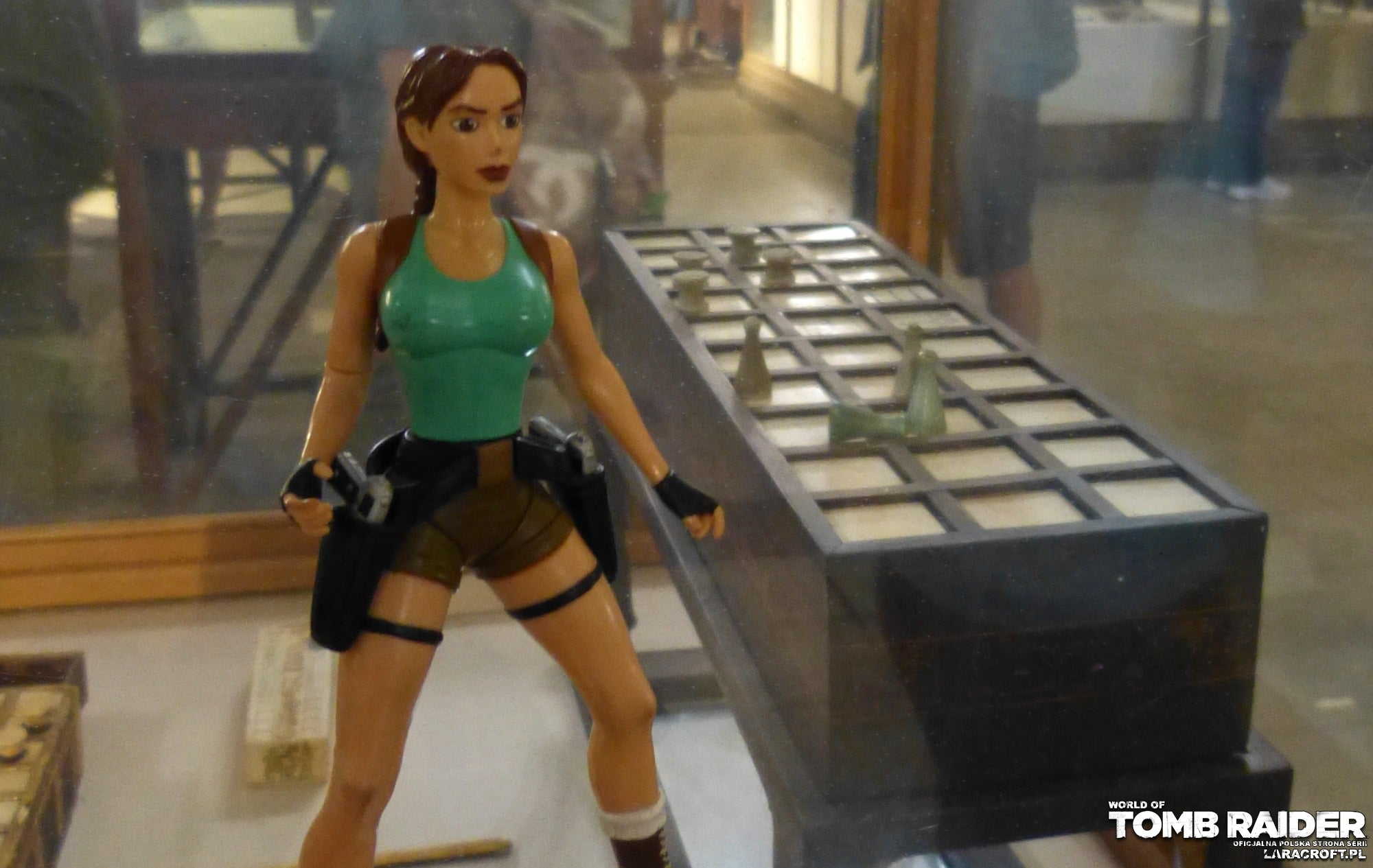 A photograph of a Lara Croft figure in front of a Senet game board in the great museum in Egypt