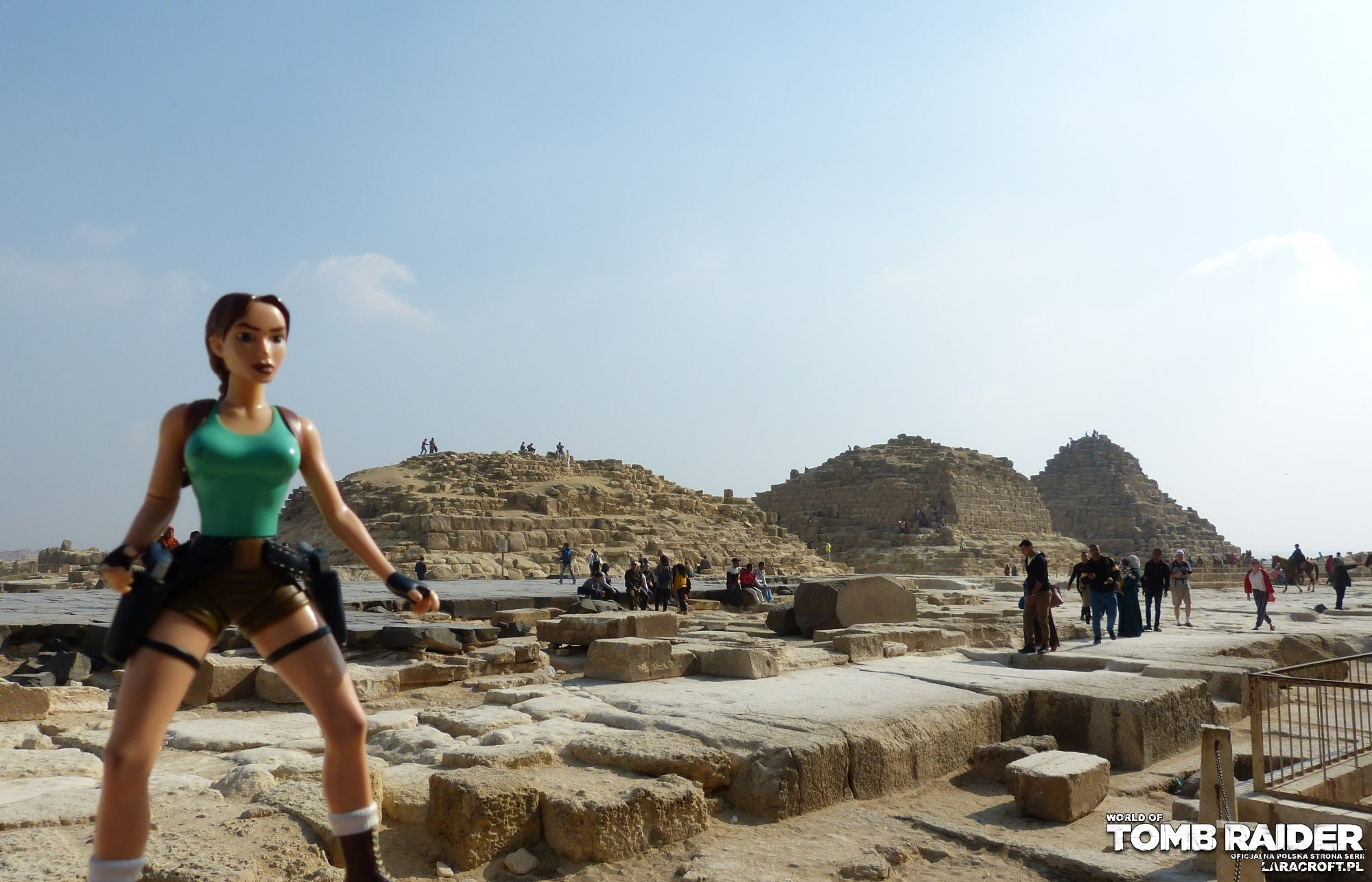 A photograph of a Lara Croft figure in front of Khufu's Queen Pyramids ruins in Egypt