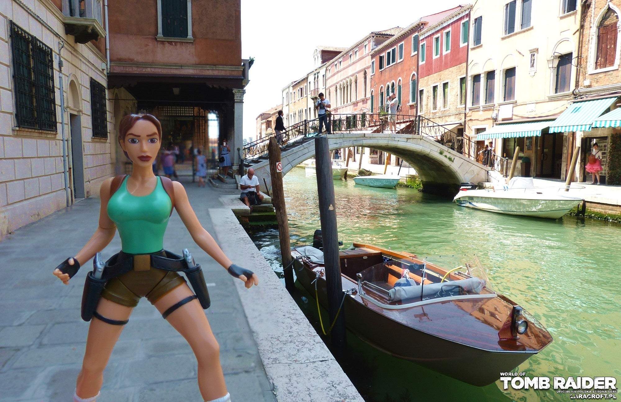 A photograph of a Lara Croft figure in front of a speedboat in Venice