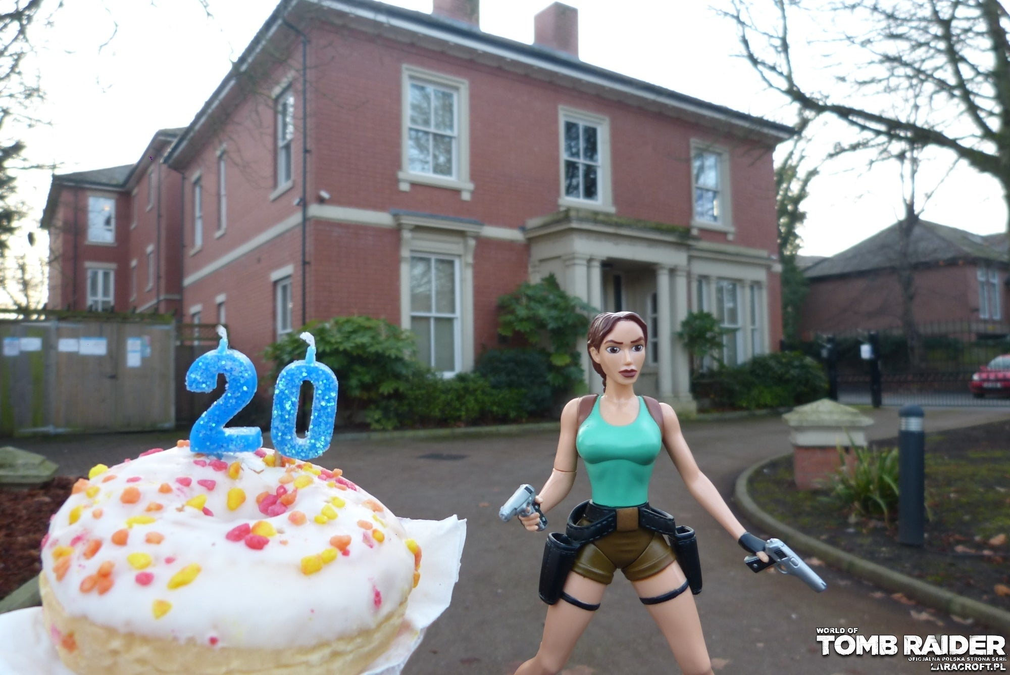 A photograph of a Lara Croft figure in front of the old Core Design Headquarters