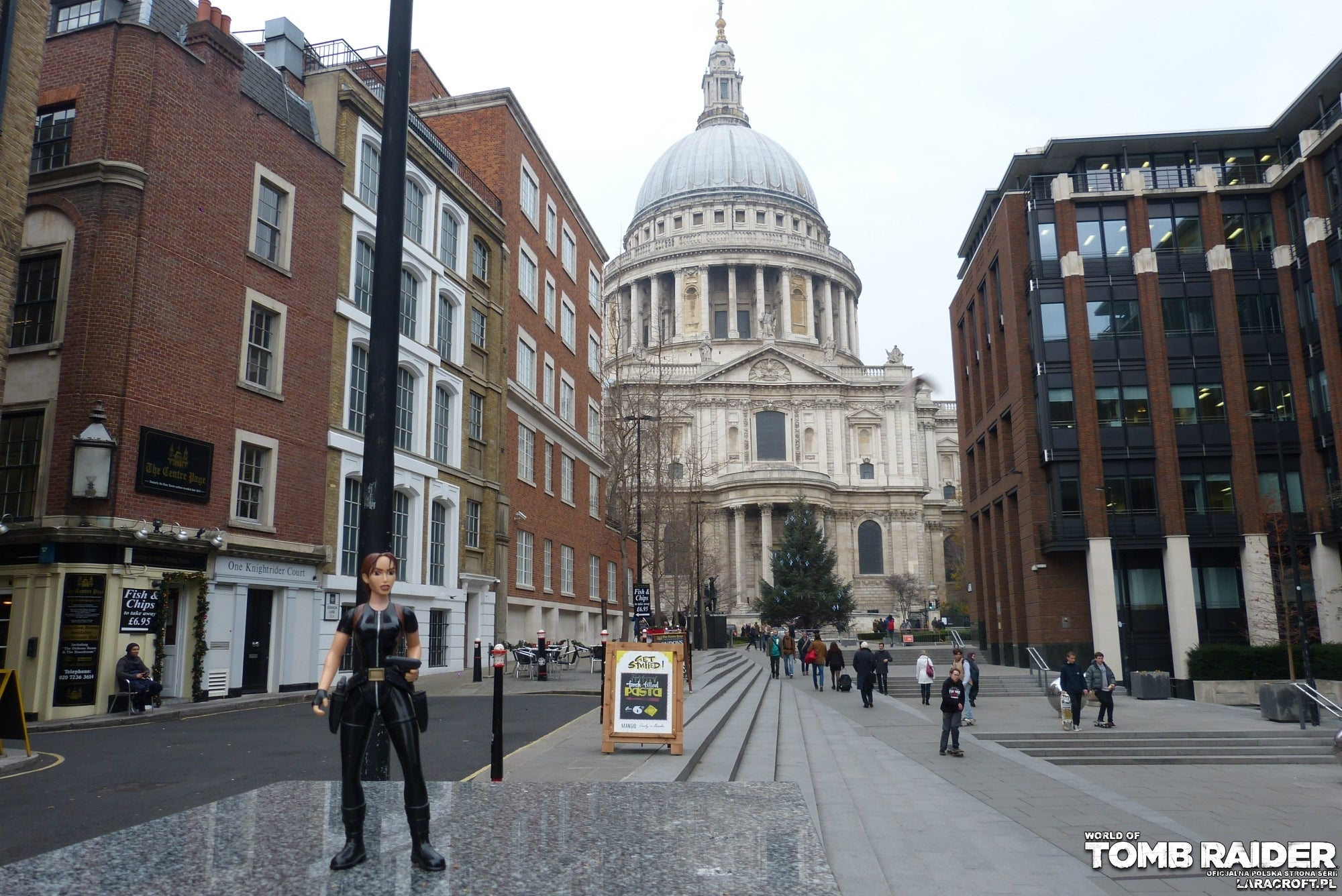A photograph of a Lara Croft figure in front of St Pauls Cathedral