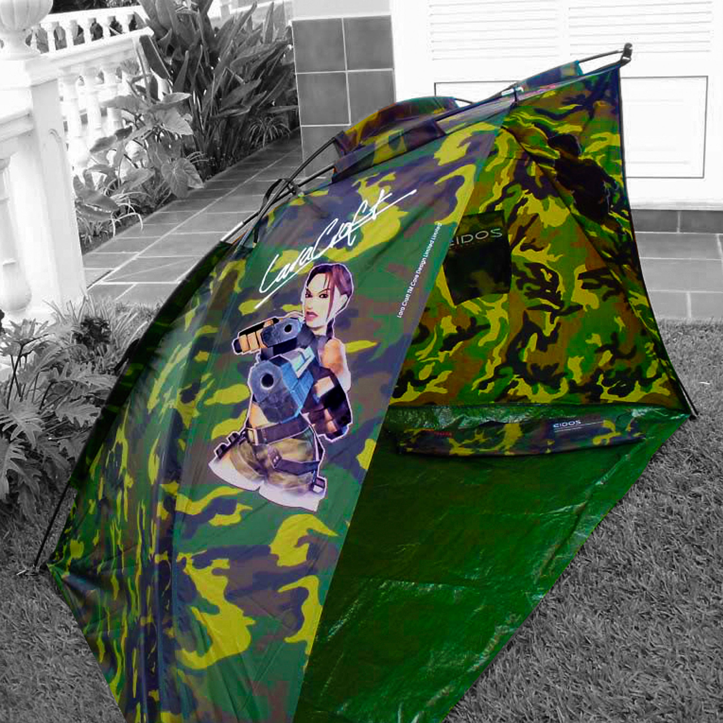 A photo of a standard green theme colored camouflage camping tent with a decal of Lara Croft from the Angel of Darkness on it and her signature