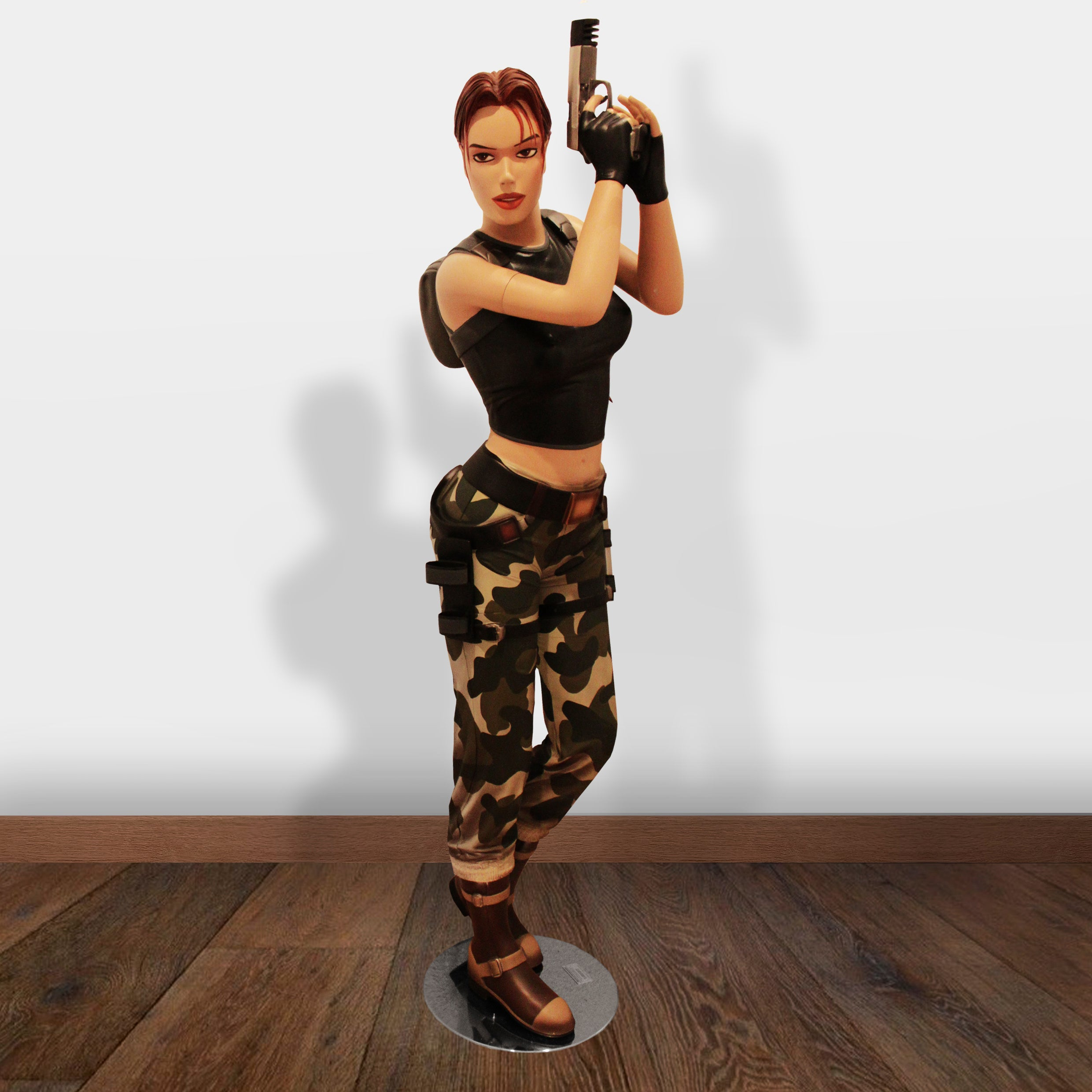 A life size statue of Lara Croft in her Angel of Darkness outfit with one pistol raised in her hands