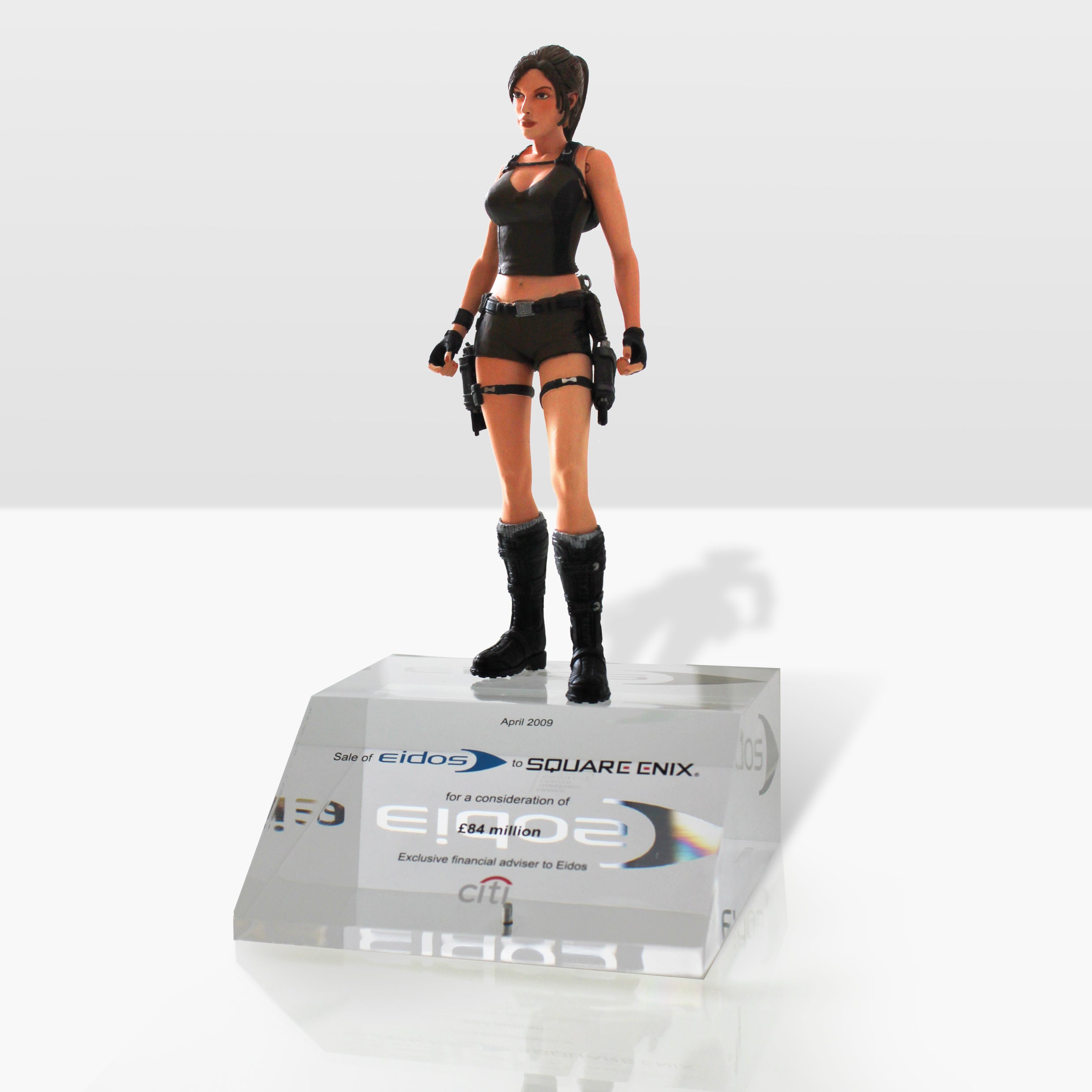 A photo of a Lara Croft figure on top of a glass base that was given to Eidos accounting employees after Square Enix acquired them