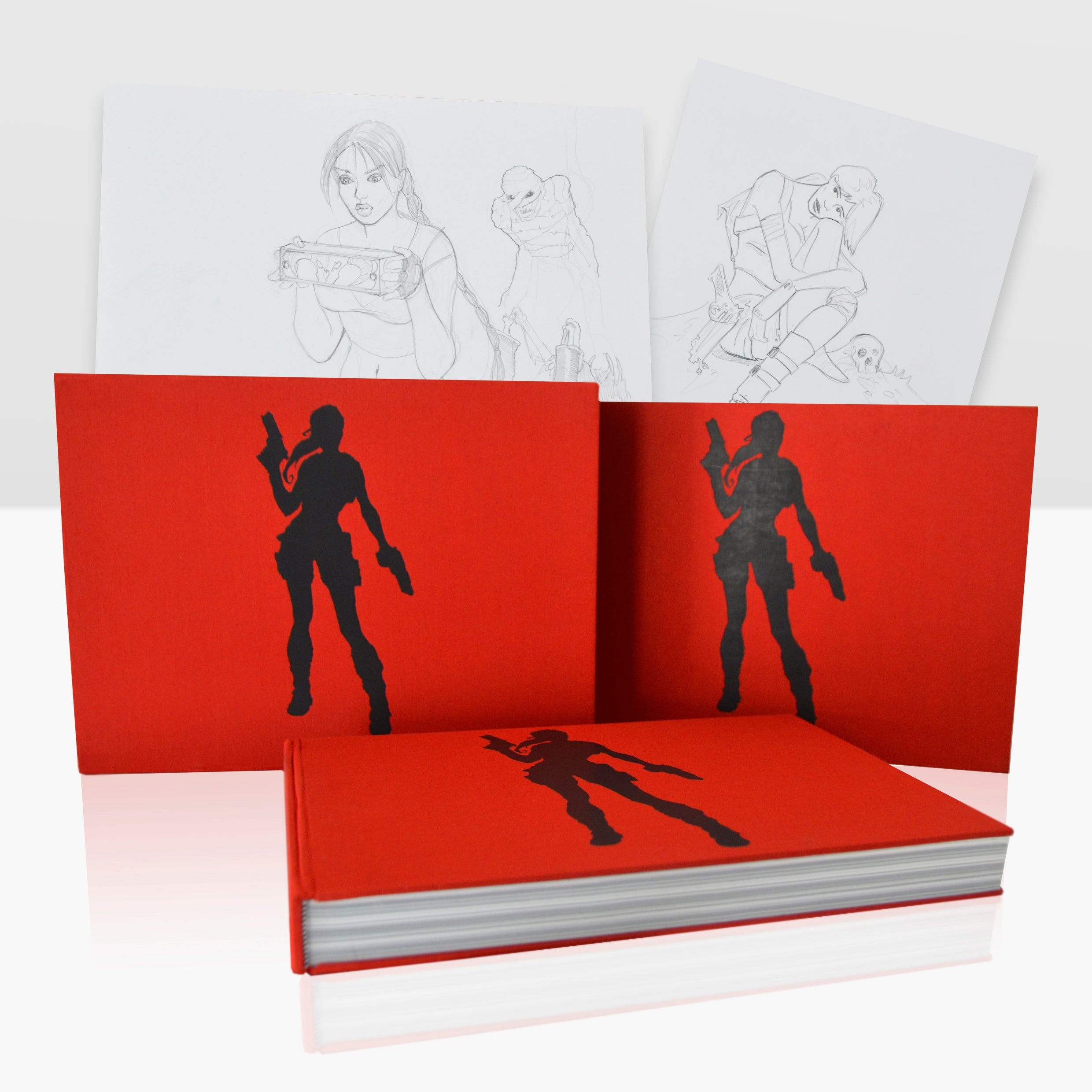 """A photo of three books of """"The Art of Tomb Raider"""" next to each other with a couple of pages in the background"""