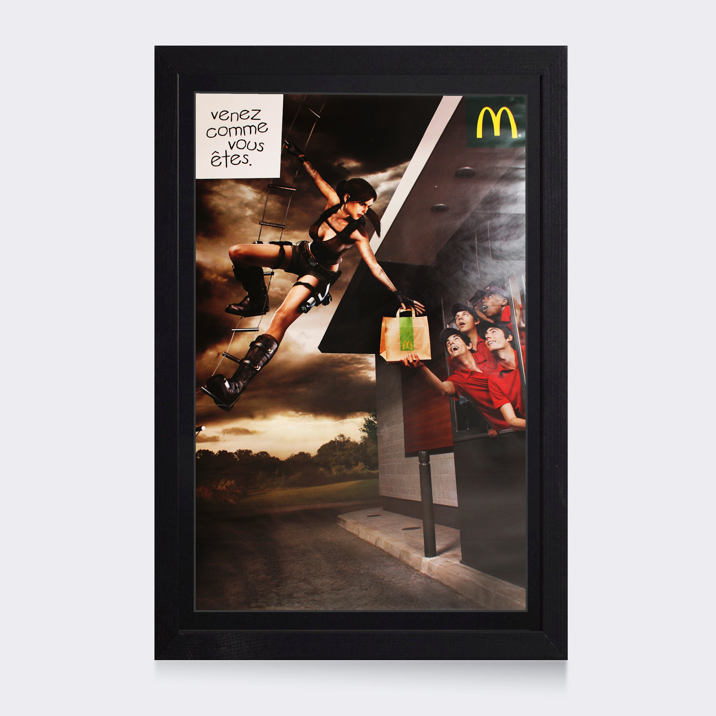 A framed poster for a French McDonald's ad featuring Lara Croft from Tomb Raider: Underworld