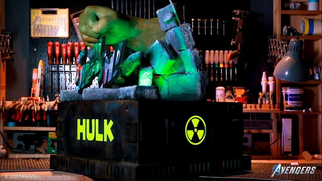 The Hulk PC build, which has a giant green fist punching through a wall atop a black square base, sits in a workshop.