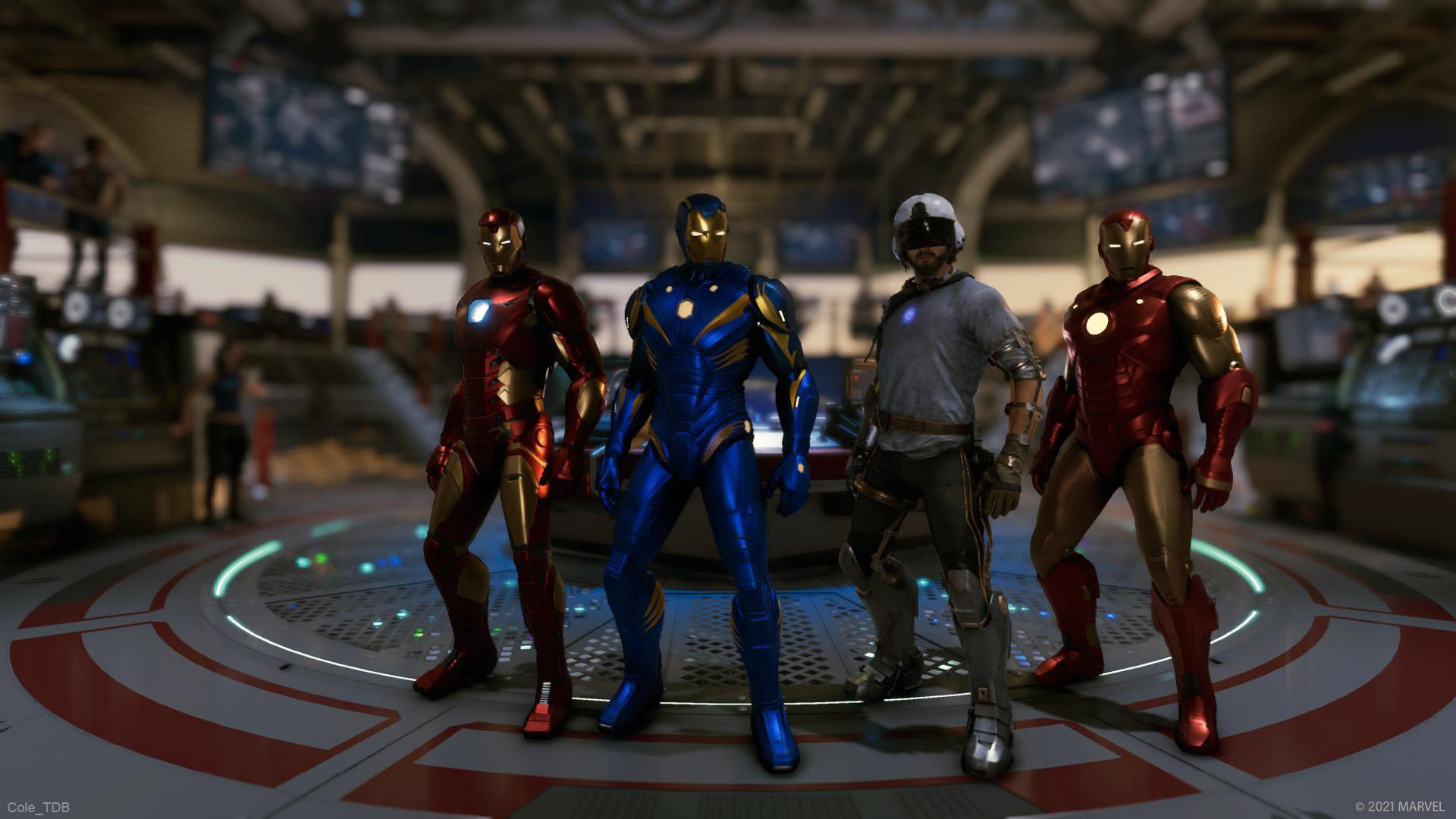 Four Iron Mans, three in shiny suits and one in the prototype build from the Reassemble Campaign, stand in front of the War Table in the Helicarrier.
