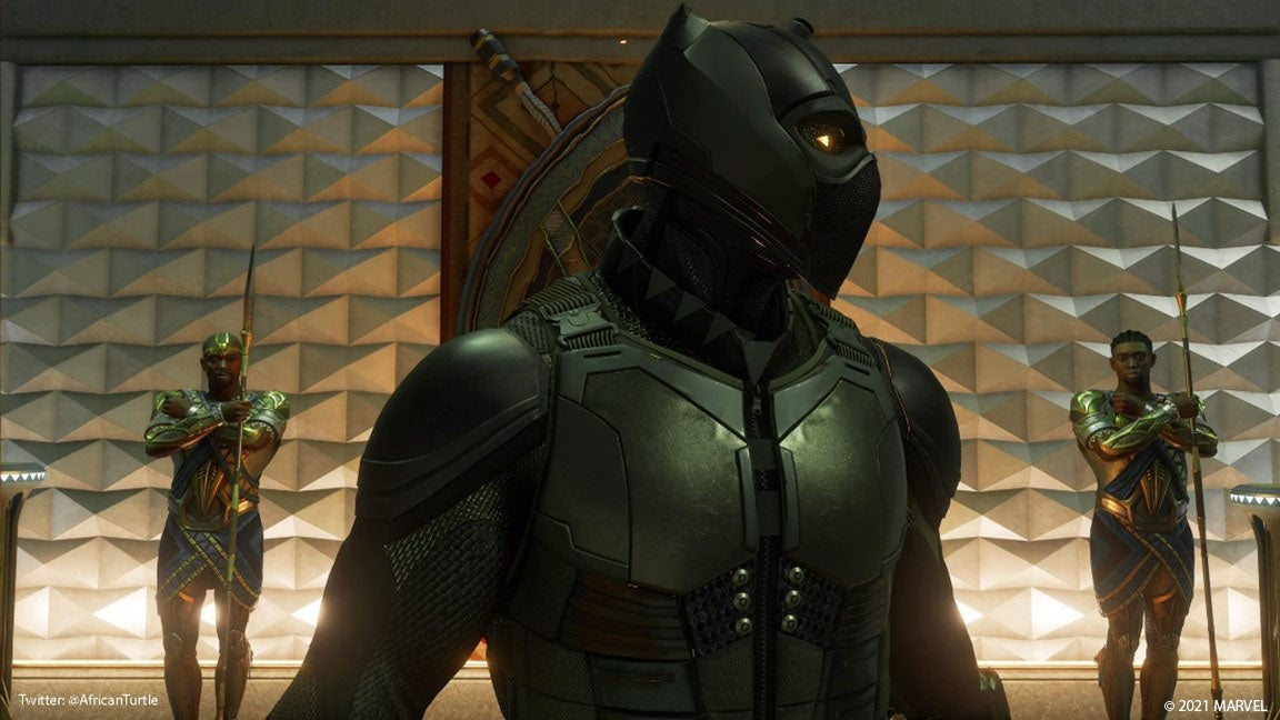 """A Community screenshot that is a close-up of T'Challa, dressed in his Black Panther outfit. He stands in a glowing hallway adorned with tribal artifacts on the wall. Behind him, two guards cross their arms in an 'X' shape – a salute that stands for the """"Wakanda Forever"""" mantra."""