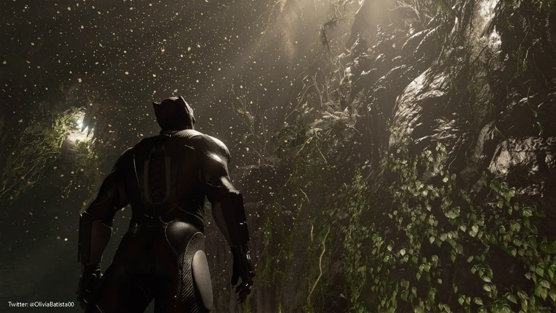 A screenshot of Black Panther in a Wakandan cave. The picture shows him from his back. He's wearing a simple black suit, and he's looking up a rocky cave wall draped in jungle ivy. Light pours over the roots of trees that have poked down into the cave's ceiling, illuminating the dust and dirt particles that feather through the air.