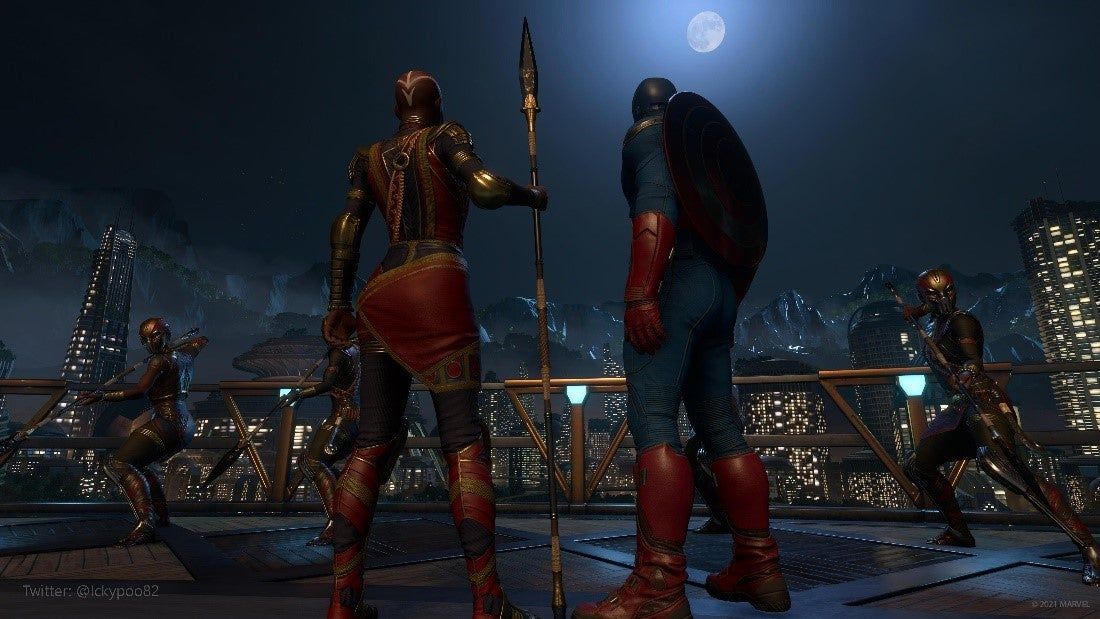 Captain America, dressed in his classic red, white, and blue Outfit, stands on a gold-laden balcony with Okoye, the captain of Wakanda's royal guard. Okoye is dressed lightly in crimson and gold, and she holds her spear as if ready to fight at any moment. She and Captain America look out across the balcony at the nighttime Wakanda skyline. The city glows in the background.