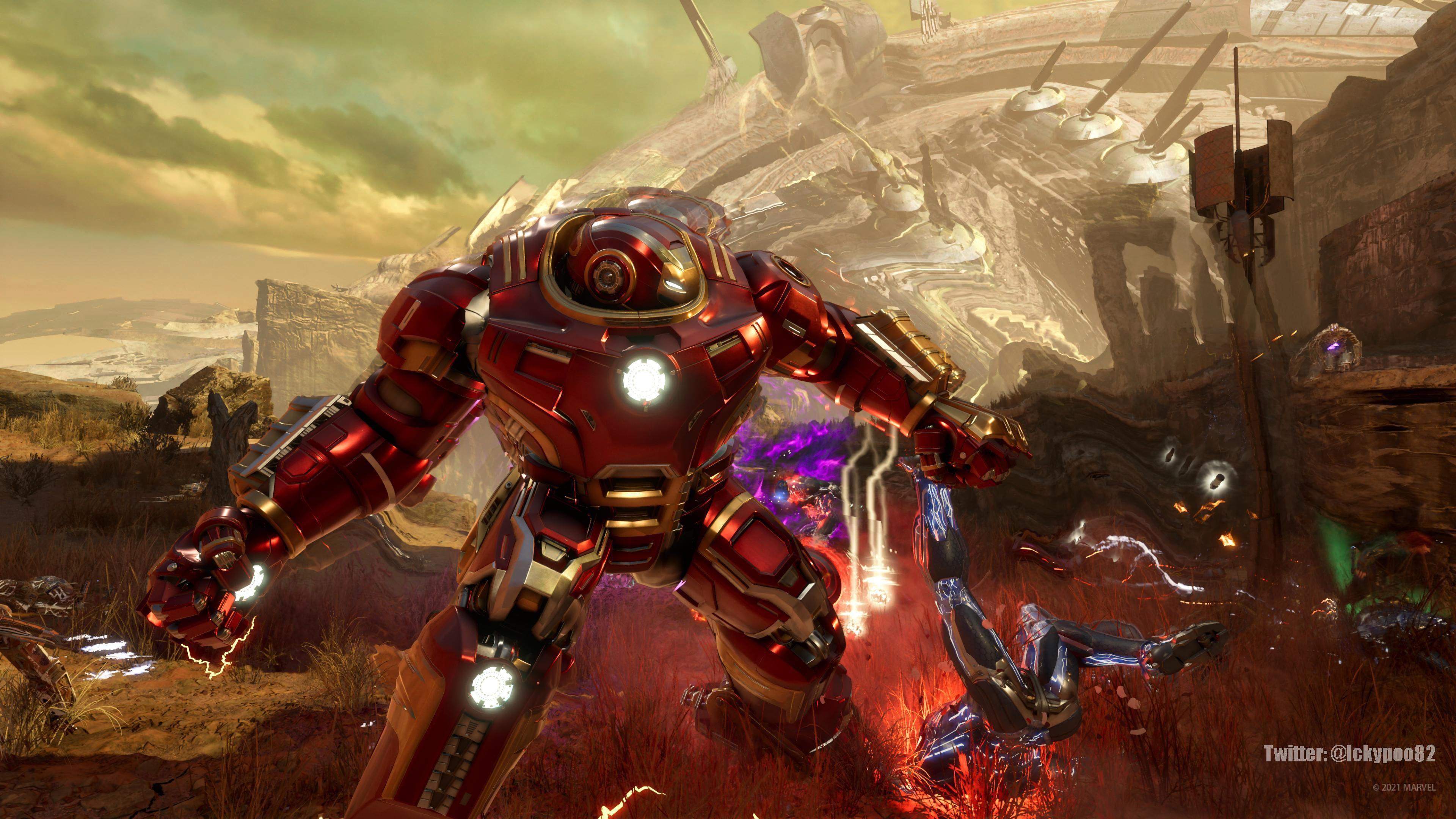 Una captura de pantalla de Iron Man con la Hulkbuster. Está en el árido páramo. Los restos de una nave alienígena enorme se vislumbran al fondo, como si de una montaña mecánica se tratase.