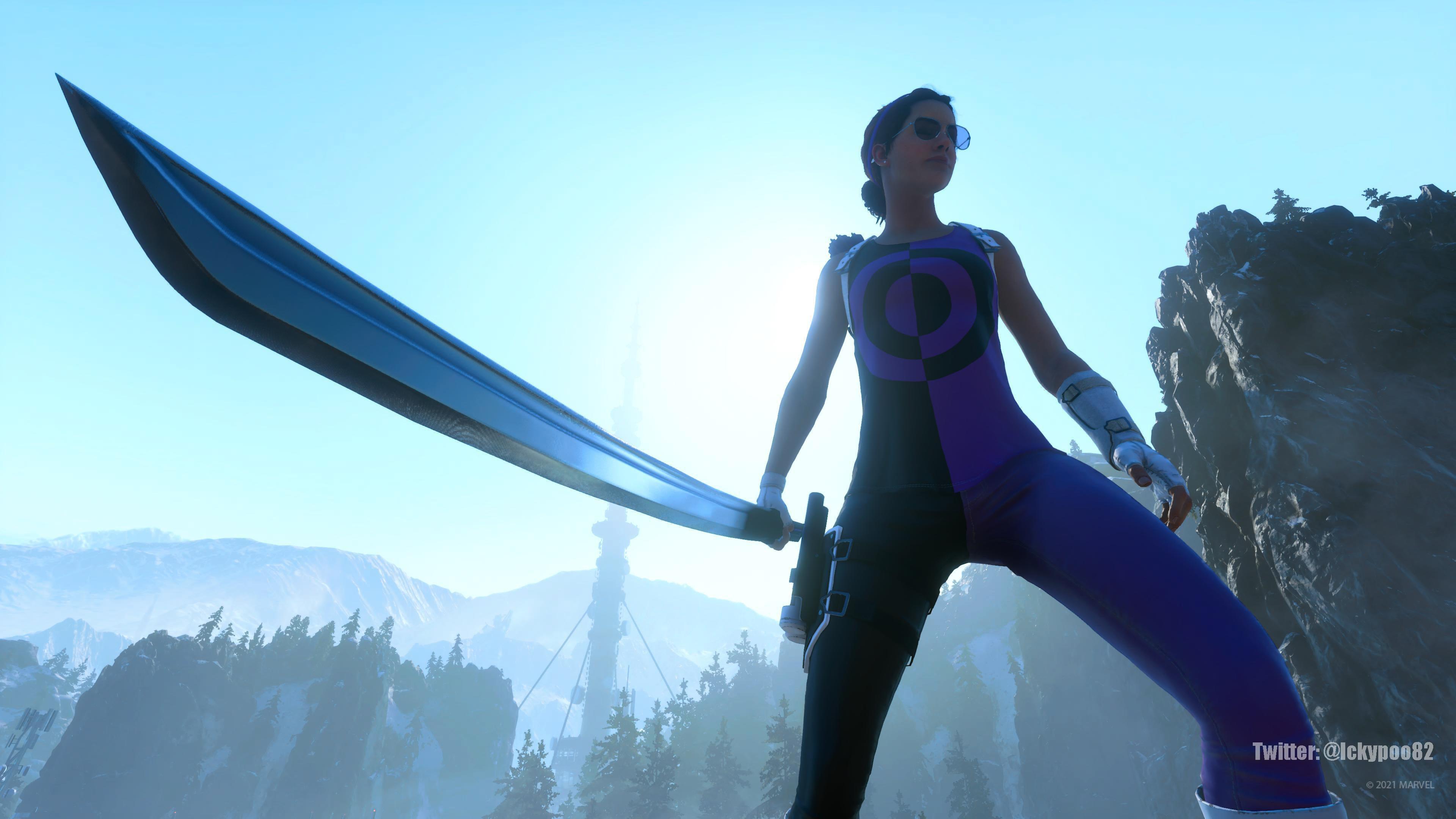 Una captura de pantalla de Kate Bishop sobre el terreno. Detrás de ella se alzan unas montañas, sobre las que vemos el despejado cielo matutino. A lo lejos, una instalación de IMA se asoma sobre un dosel de árboles en la montaña. Kate sujeta su espada a un lado, lista para enfrentarse al enemigo.