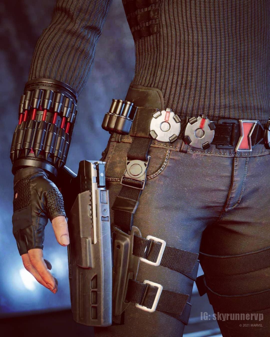 """A screenshot closeup of Black Widow's tool belt. A black pistol sits snug in its hip holster. She wears her """"Widow's Bite"""" around her wrist, which is a series of small red and black mini rockets that strike enemies with electroshock damage. Her belt buckle is the iconic red hourglass symbol of the black widow spider."""