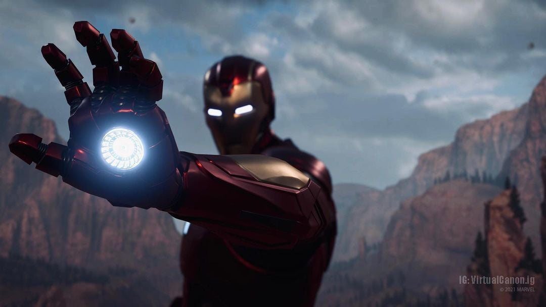 A screenshot of Iron Man holding out his red-armored repulsor gauntlet. His palm glows with blue arc reactor energy. He stares down an unseen foe. Behind him, rocky, barren mountains rise behind him. The sky is partially cloudy, as if it's about to rain.